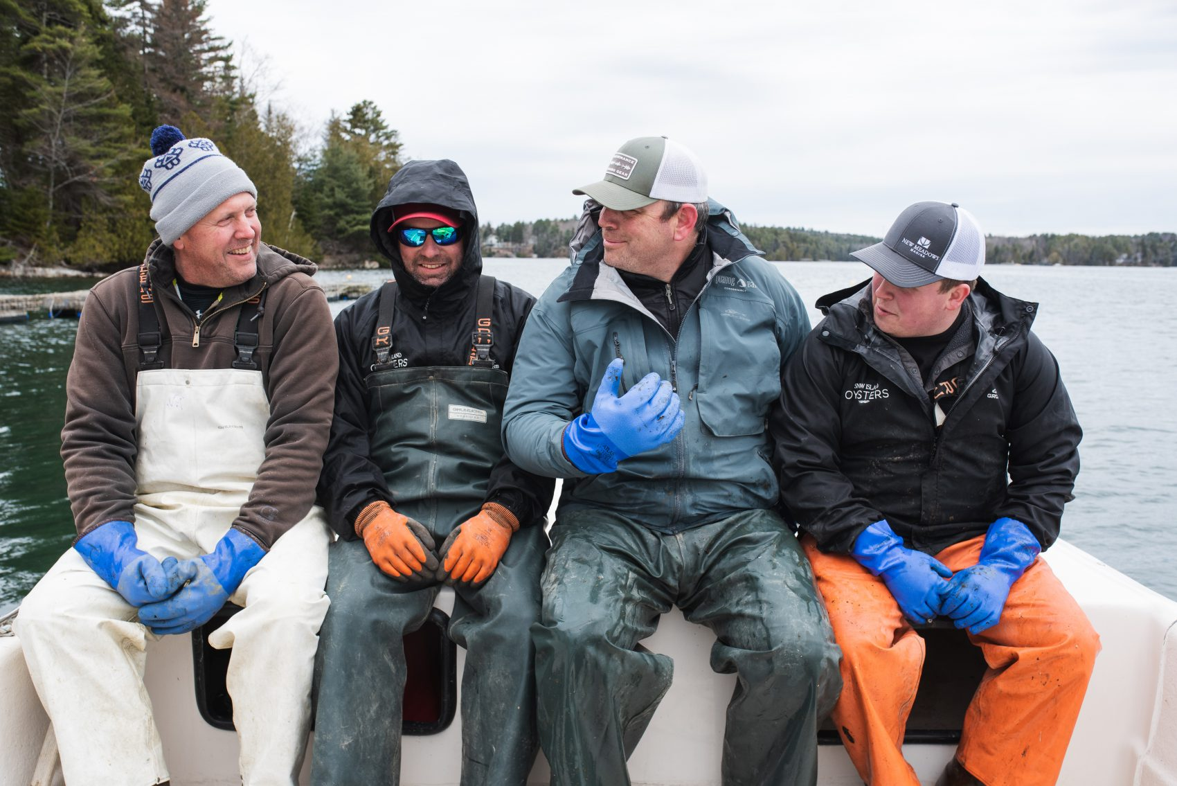 Peter, Donnie, Dave and Alec of Snow Island Oysters sit next to one another on the bow of their boat.